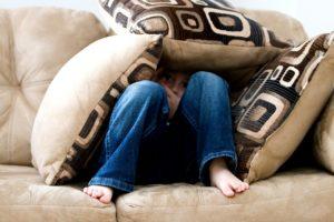 image of a boy hiding behind cushions on a sofa in fear